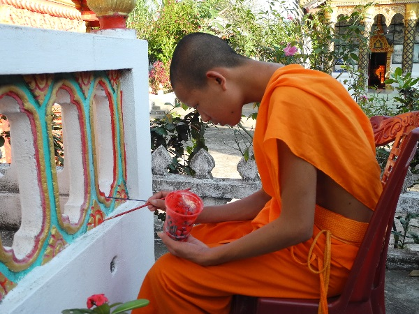 Laos, Mönch verschönt Tempel