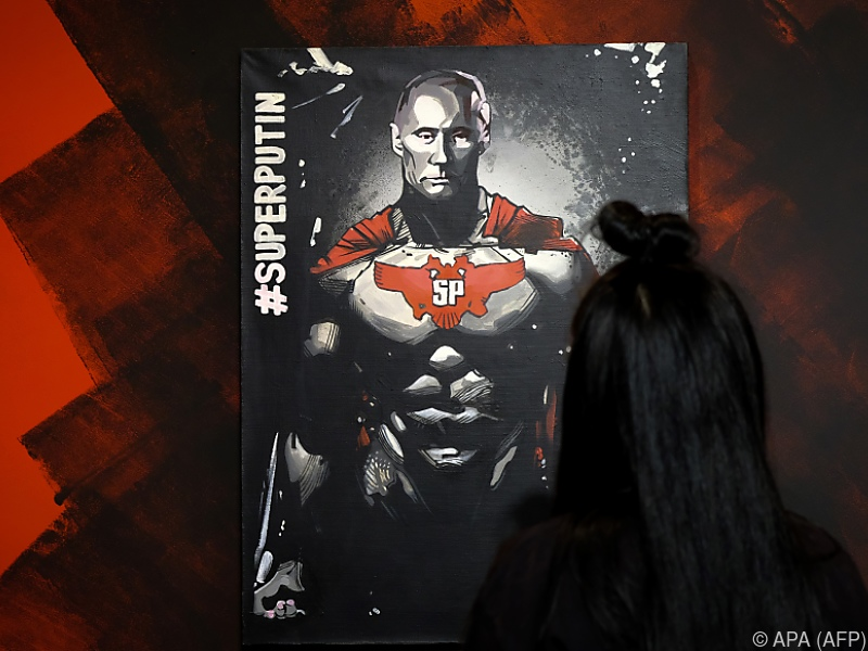 "A woman looks at a painting depicting Russian president Vladimir Putin at the ""SUPERPUTIN"" exhibition at UMAM museum in Moscow on December 6, 2017. / AFP PHOTO / Yuri KADOBNOV / RESTRICTED TO EDITORIAL USE - TO ILLUSTRATE THE EVENT AS SPECIFIED IN THE CAPTION"
